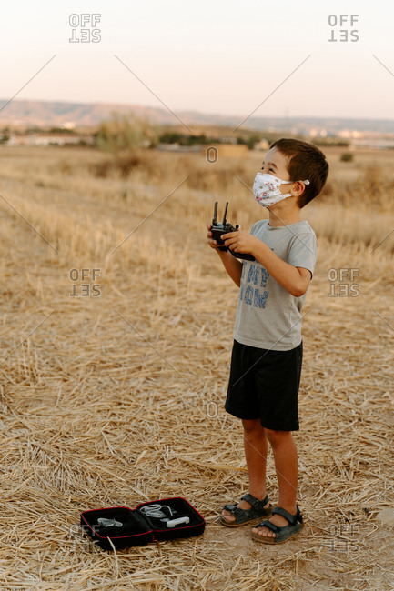 Little Asian boy in protective mask using remote control while playing with flying drone in field