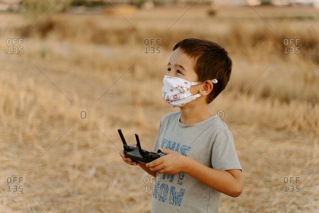 Side view of focused little Asian boy in protective mask using remote control while playing with flying drone in field
