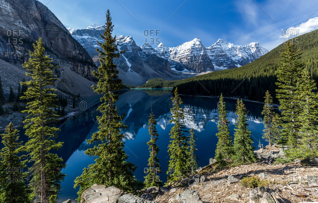 Magnificent scenery of beautiful lake with clean plain water reflecting rocky mountains and green forest in sunny day in Duffey Lake Provincial Park in Canada