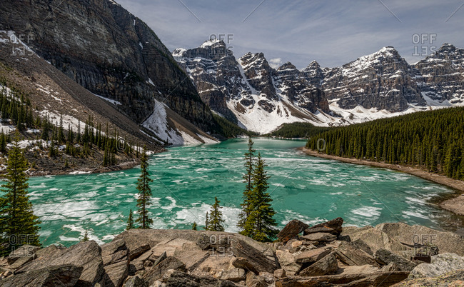 Majestic scenery of frozen Moraine Lake surrounded by green coniferous forest and rough rocky mountains covered with snow in cloudy day in Banff National Park in Canada
