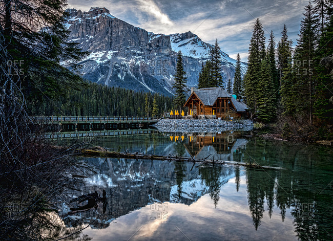 Magnificent scenery of Emerald Lake with bridge over water and wooden house on shore surrounded by green pine forest against rocky mountains covered with snow in Yoho National Park in Canada