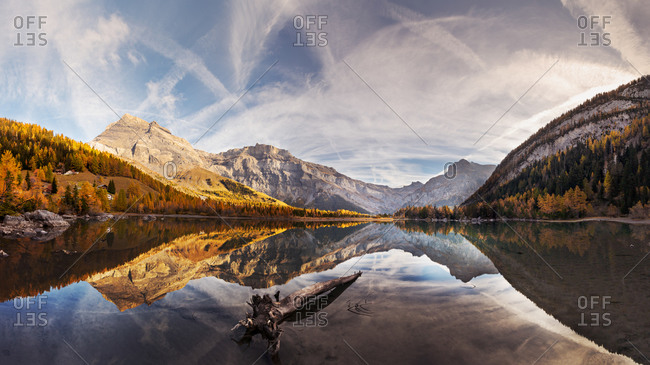 Spectacular scenery of lake with smooth surface reflecting amazing mountain range and sky