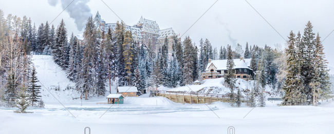 Panoramic landscape with village buildings surrounded by coniferous trees on hilly terrain covered with snow in wintertime