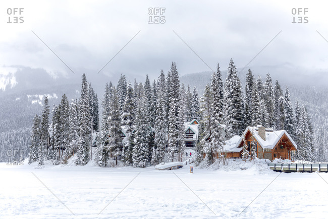 Picturesque winter landscape of snowy valley with wooden house surrounded by coniferous woods and rocky mountains under cloudy sky