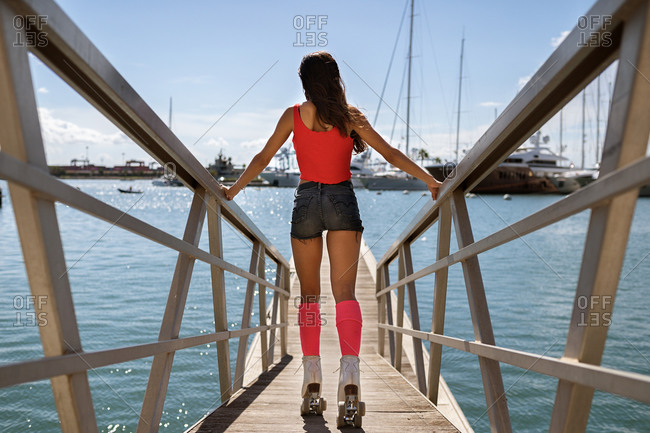 Back view of unrecognizable slender female roller skating along wooden quay in city in summer