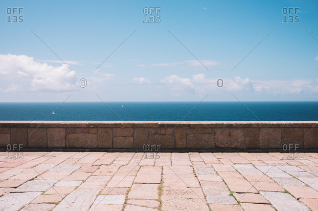 Empty stone embankment with border against calm sea and cloudy blue sky on Cape Vilan peninsula in Spain