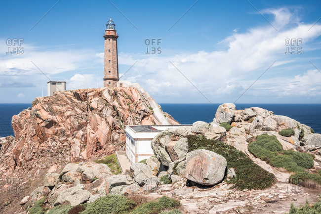 Picturesque scenery with old lighthouse tower and houses located on rough rocky cliff near sea on Cape Vilan peninsula on Spanish coast against cloudy blue sky in summer day