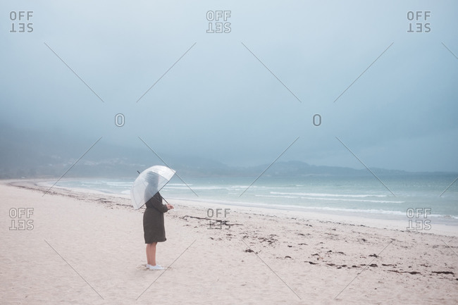 Side view of unrecognizable traveler in raincoat with transparent umbrella walking on empty sandy beach towards waving sea in cloudy day