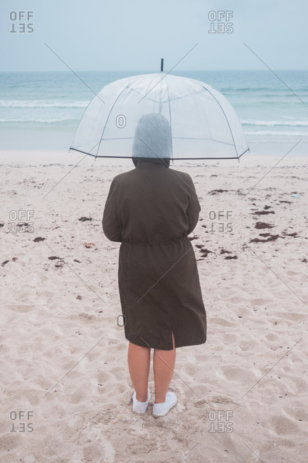 Back view of unrecognizable traveler in raincoat with transparent umbrella walking on empty sandy beach towards waving sea in cloudy day