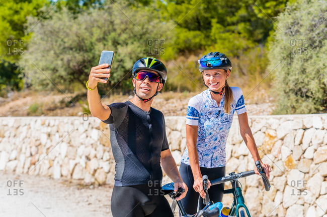 Happy young active man and woman in sportswear and protective helmets taking selfie on smartphone while standing with bikes on country road and preparing for riding