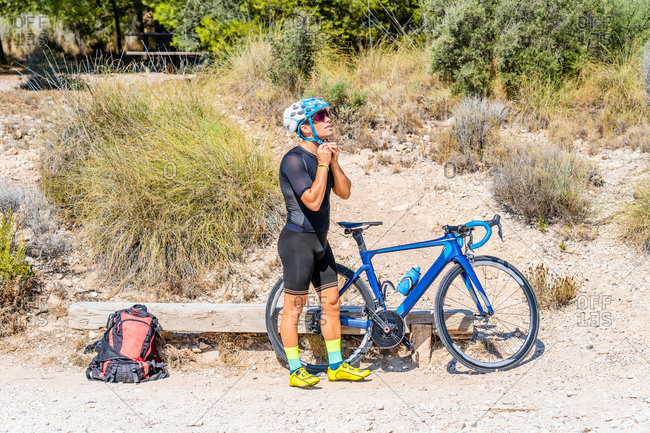 Full body side view of sporty male bicyclist in activewear with backpack standing near bike and adjusting helmet while preparing for riding workout in summer nature