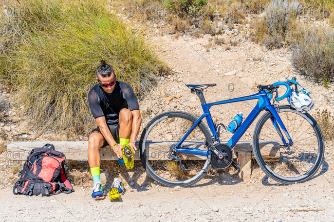 Full length of active male bicyclist in sportswear sitting on wooden bench and putting on cycling shoes while preparing for mountain bike ride