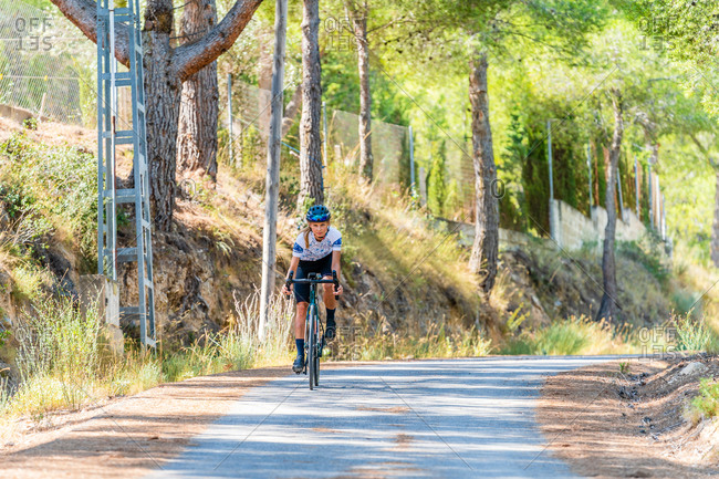 Full length of active female bicyclist in helmet and sportswear riding bike on asphalt road near mountain ridge in summer day