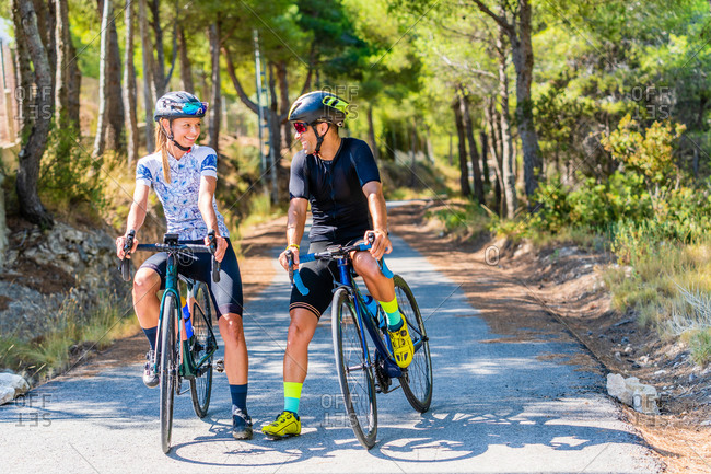 Full body of happy sportive man and woman in activewear and helmets standing with bicycles on asphalt roadway and resting during ride through mountainous area in summer day