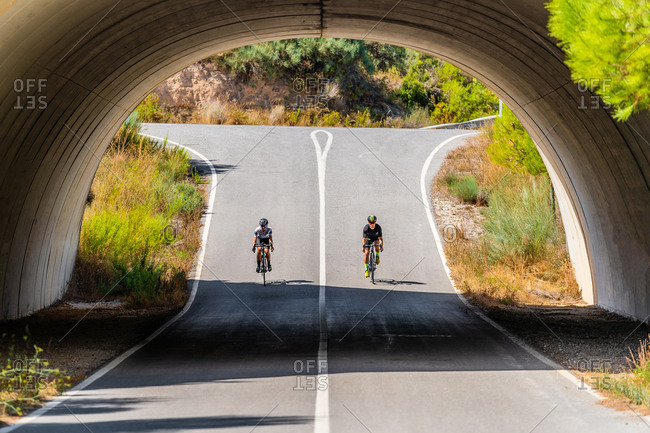 Full length of distant unrecognizable bicyclists in sportswear and helmets cycling together on asphalt roadway under arched bridge in summer countryside