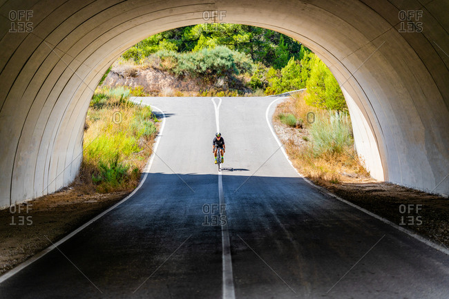 Full length of bicyclist in sportswear and helmet cycling on asphalt roadway under arched bridge in summer countryside