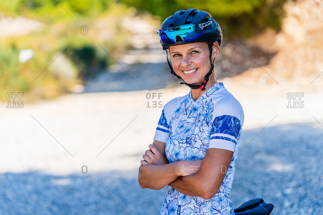Portrait of cheerful woman bicyclist in sport clothes with crossed arms looking at camera