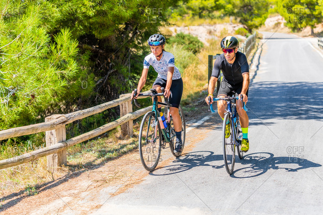 Full length of bicyclists in sportswear and helmets cycling together on asphalt roadway in summer countryside