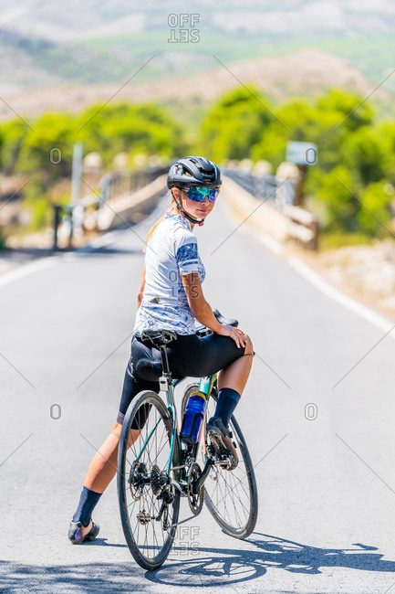 Woman bicyclist in sportswear and helmet resting on road while riding bike up paved road in rural mountainous area