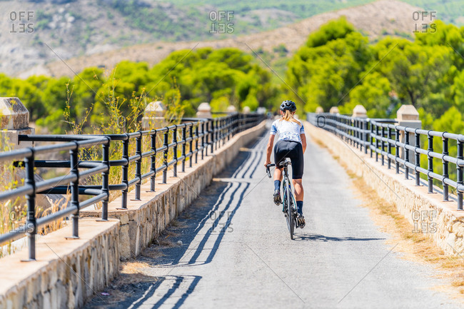 Full body back view of fit female cyclist in sportswear and helmet riding bike on narrow curved road leading through green forest in summer day