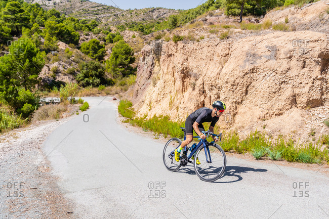 Full length of strong male bicyclist riding bike on curvy paved road going up among mountains