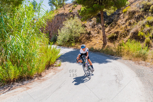 Full length of strong female bicyclist riding bike on curvy paved road going up among mountains
