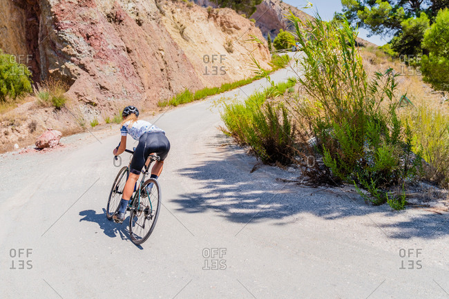 Full length back view of anonymous strong female bicyclist riding bike on curvy paved road going up among mountains