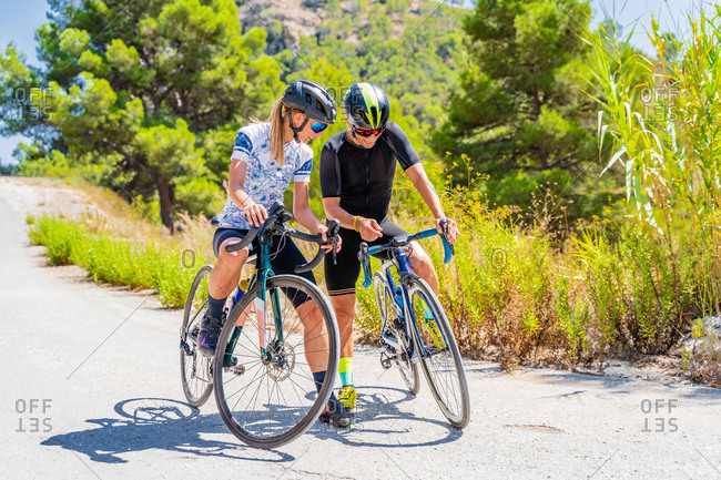 Full length of sportive man and woman checking GPS navigator while riding bicycles through forested mountainous terrain
