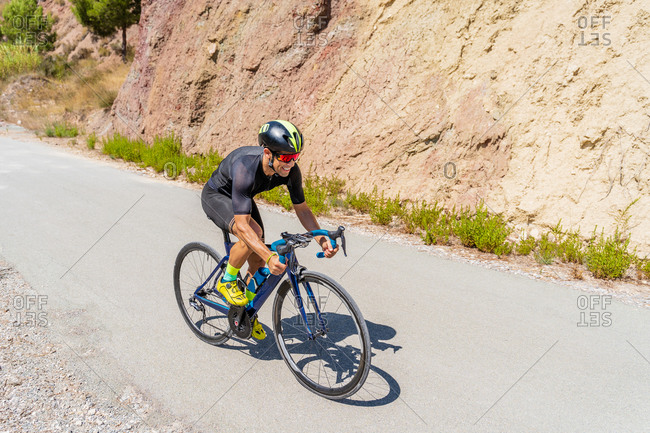 Full length of strong male bicyclist riding bike on curvy paved road going uphill among mountains