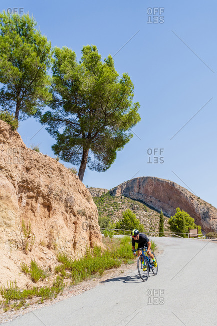 Full length of strong male bicyclist riding bike on curvy paved road going downhill among mountains
