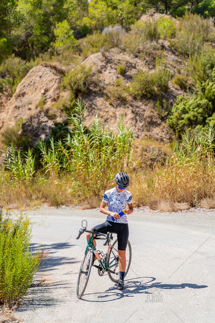 Full body of fit female bicyclist in sportswear and helmet drinking fresh water from bottle while resting after riding bike up mountain road