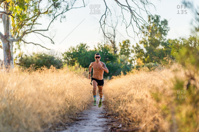 Full body shirtless male athlete with sunglasses running on narrow footpath among tall grass during outdoor workout in nature