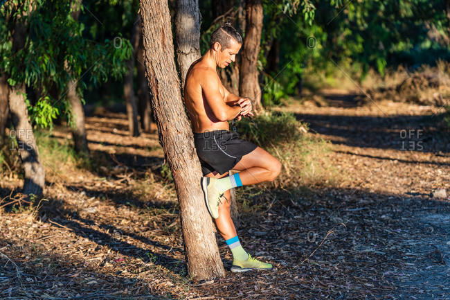 Full body side view of strong shirtless sportsman leaning against tree trunk and checking results on fitness tracker while having break during running in park