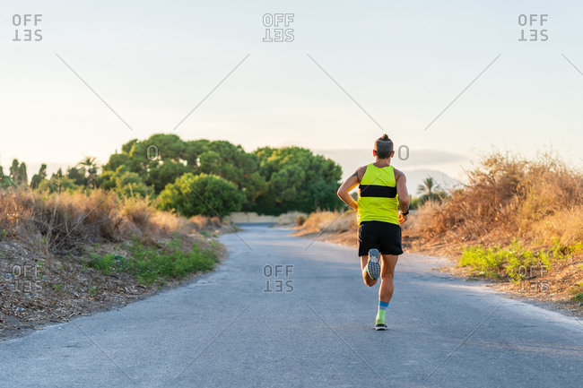 Back view of unrecognizable sportive male athlete in activewear running along path in park during cardio workout in summer