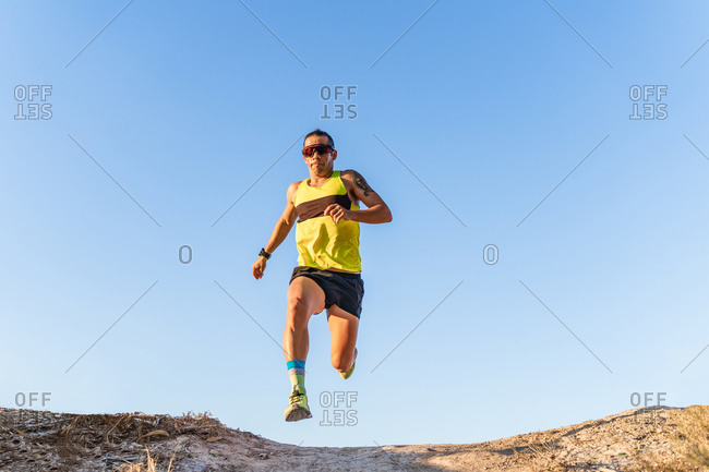 From below full body of energetic athletic male in sportswear and sunglasses jumping and running against cloudless blue sky