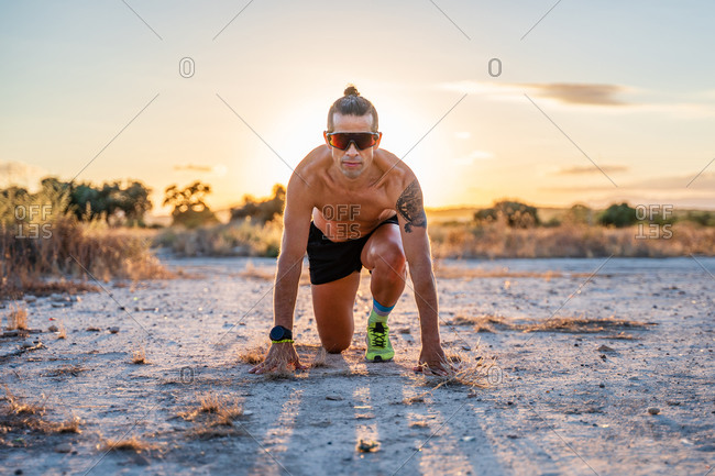 Determined male athlete with naked torso standing in crouch start position and getting ready for run during training in countryside while looking at camera