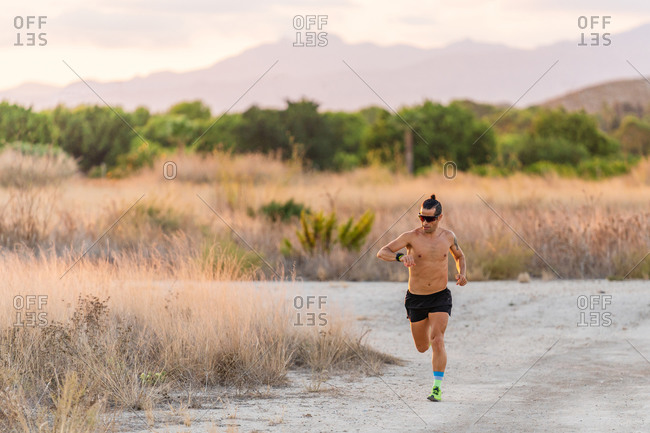 Active male athlete with strong body running along rural road and checking time on wristwatch during intense training in summer
