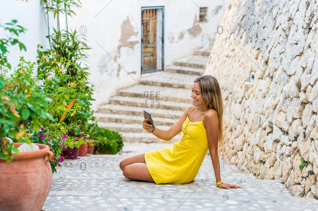 Side view of cheerful young female in bright yellow sundress sitting on stone steps and taking selfie on smartphone while resting during sightseeing in old town