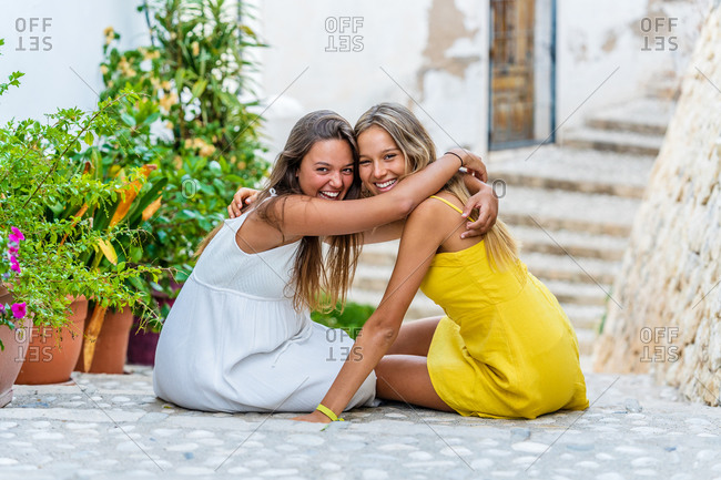 Full length side view of cheerful young female friends in stylish dresses sitting together on stone stairs near ancient building during summer vacation in old town