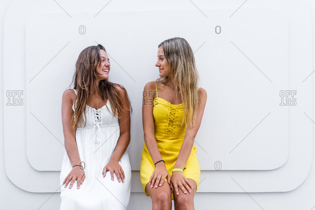 Positive female friends wearing summer clothes leaning on modern building during city stroll