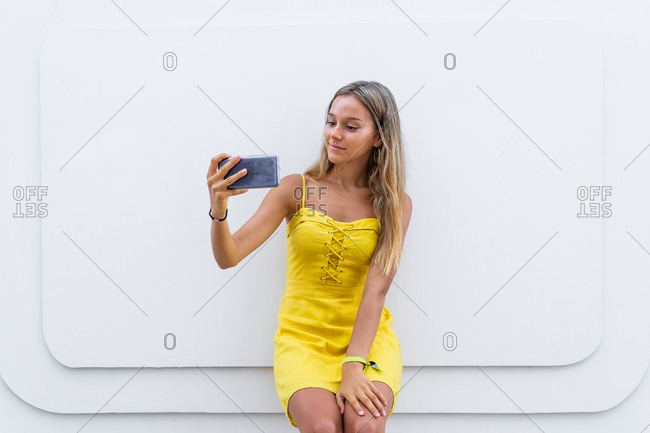 Glad female in yellow summer dress leaning on building on street and browsing mobile phone during city stroll
