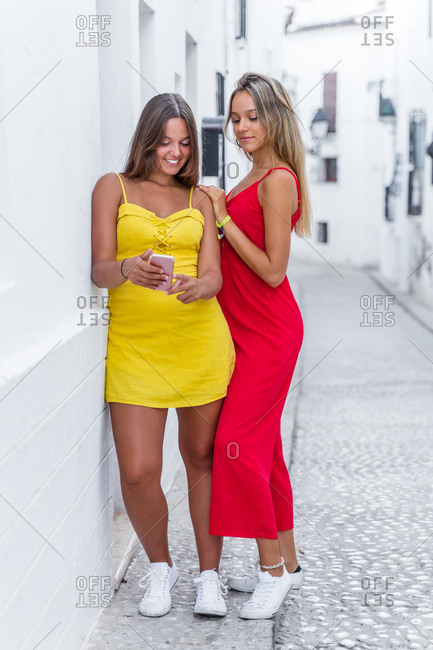 Positive female friends wearing summer clothes standing near building on narrow street and reading messages together on cellphone during summer stroll