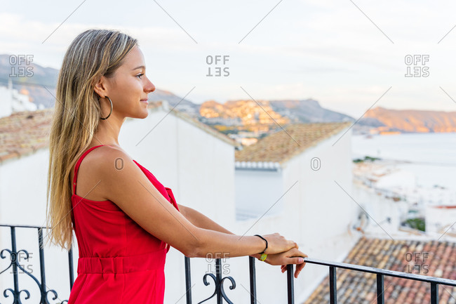 Side view of carefree female tourist standing on terrace and leaning on railing while enjoying amazing cityscape at sunset during vacation in summer