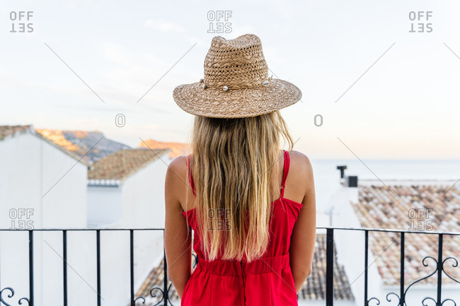 Back view of unrecognizable female tourist standing with straw hat in raised hand on terrace and enjoying summer vacation while admiring amazing cityscape