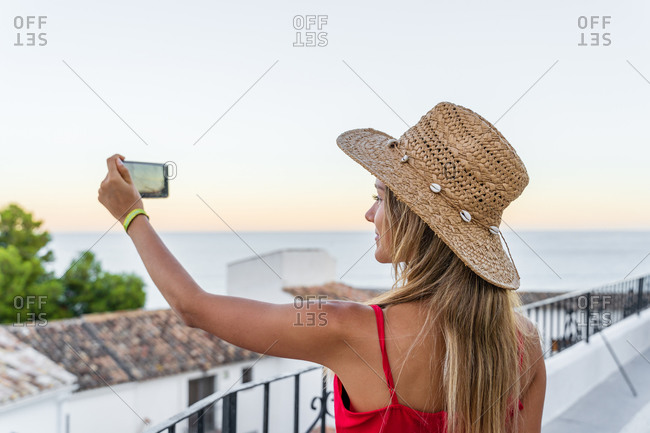 Side view of female tourist in sunhat standing on terrace with smartphone and taking picture of spectacular view of coastal city under sundown sky in evening