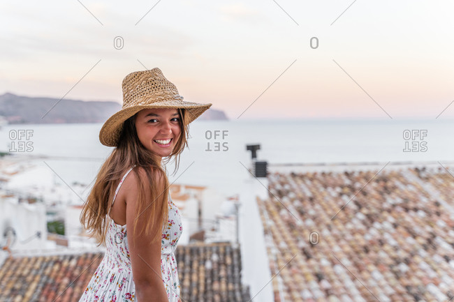 Side view of cheerful female tourist in summer dress and straw hat standing on background of old city near sea and looking at camera at sunset