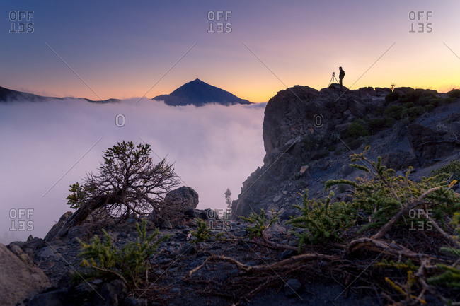 Side view of anonymous photographer explorer standing on rock and observing majestic scenery of mountains under thick fog in morning during vacation in Tenerife