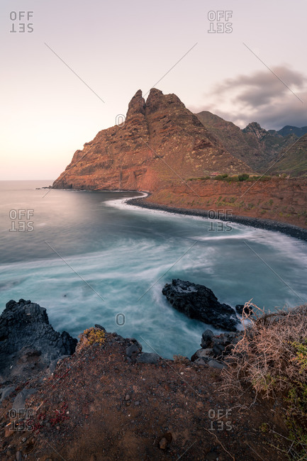 Wonderful scenery of rocky coast and calm sea under sundown sky in long exposure in evening in Tenerife