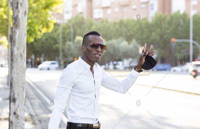 Stylish African American male entrepreneur standing on roadside and catching taxi while looking forward