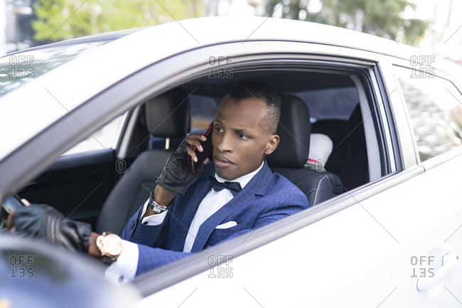 Serious ethnic male entrepreneur in classy suit with bow tie driving luxury car while talking on smartphone and looking away